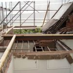 Deconstruction of the original roof showing existing structure being built up to new roof level