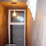 The hallway after replastering, showing the preservation of original features like the corbels